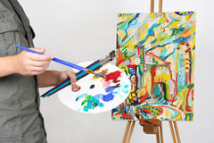 Man holding brushes and palette, painting Royalty Free Stock Images