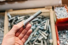 A man is holding a building bolt. Many different fastening tools used in construction and repair. A man is holding a bolt. Many different fastening tools used Stock Photo