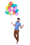 Man holding a bunch of balloons is inviting to party Stock Image