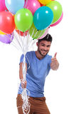 Man holding a bunch of balloons and making ok Stock Photos