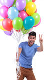 Man holding a bunch of balloons and making victory sign Royalty Free Stock Photography