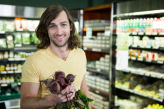 Man holding bunch of beetroots in supermarket Stock Photography
