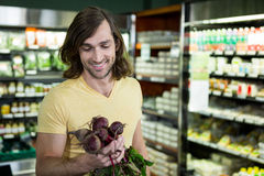 Man holding bunch of beetroots in supermarket Stock Photo