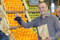 Man holding bunch grapes in store Royalty Free Stock Image