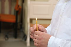 Man holding a Burning candle in a church Stock Images