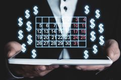 Man holding calendar and dollar signs. royalty free stock image
