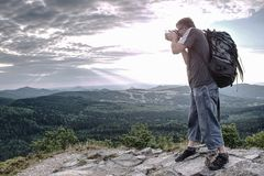 Man holding camera at eyes on mountain royalty free stock images