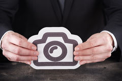 Man holding camera icon in hands Royalty Free Stock Photos