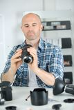 Man holding camera lens. Man holding a camera lens Royalty Free Stock Images