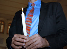Man holding candle. A man holding a lit candle in a ceremony Stock Photos