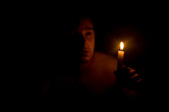 Man holding candle in dark. The dim outline of a man holding one small candle in a very dark room Stock Photos