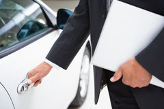 Man holding a car door handles while holding clipboard Royalty Free Stock Images