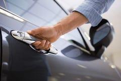 Man holding a car door handles Stock Images