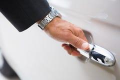 Man holding a car door handles Stock Photo