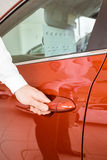 Man holding a car door handles Royalty Free Stock Image