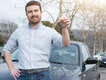 Man holding a car key next to his vehicle Royalty Free Stock Photo
