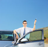 Man holding a car key on an open road Royalty Free Stock Photography