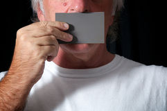 Man holding card over mouth. Close up of a man holding a grey card over his mouth against a black background wearing white t shirt. Censorship or freedom of Royalty Free Stock Images