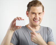 Man holding card. Patriyoung man holding and showing blank card k Chmelik Stock Photos