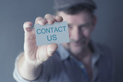 Man holding card with the words Contact Us. Man holding up a card with the words Contact Us Royalty Free Stock Images