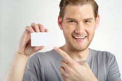 Man holding card. Young man holding and showing blank card Royalty Free Stock Photography