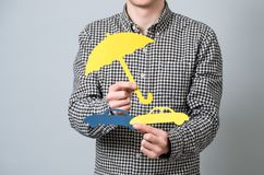 Man holding paper symbols. Man holding cardboard blue model of cars and yellow umbrella. Concept for vehicle insurance Stock Image