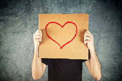 Man holding cardboard paper with heart shape drawing Royalty Free Stock Photos