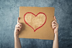 Man holding cardboard paper with heart shape drawing Royalty Free Stock Image