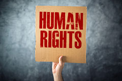 Man holding cardboard paper with HUMAN RIGHTS title Stock Images
