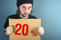 Man holding cardboard paper with sales discount price. Man holding cardboard paper with twenty percent sales discount price. Consumerism concept, retail store Stock Images