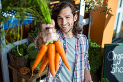 Man holding carrots in organic shop Royalty Free Stock Images