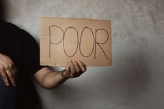 Man holding carton sign with word POOR on grey background. Closeup royalty free stock photography