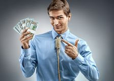 Man holding cash money and pointing a finger at them. Photo of smiling man in blue shirt and tie in the form of loop on his neck on grey background Stock Photo