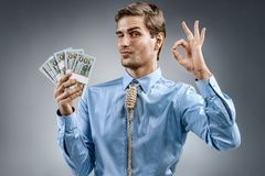 Man holding cash money and showing okay sign. Photo of smiling man in blue shirt and tie in the form of loop on his neck on grey background Royalty Free Stock Photos