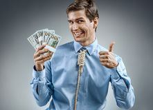 Man holding cash money and showing thumb up. Photo of smiling man in blue shirt and tie in the form of loop on his neck on grey background Stock Images