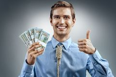Man holding cash money and showing thumb up. Photo of smiling man in blue shirt and tie in the form of loop on his neck on grey background Stock Photos
