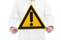 Man holding a caution sign with exclamation point stock images