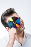Man holding a cd. Man in shirt standing smiling looking through CD - isolated on white Royalty Free Stock Image