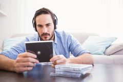 Man holding cd while listening to music. In the living room Stock Images