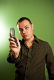Man holding cell phone. Attractive man holding cell phone; against green background Stock Photo