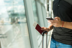 Man holding cell phone, passports and boarding Royalty Free Stock Photo