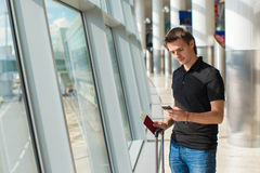 Man holding cell phone, passports and boarding Stock Photos