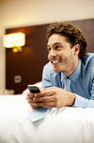 Man holding cellphone and lying on bed, relaxed Royalty Free Stock Photo