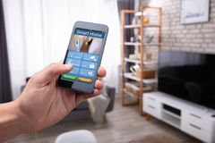 Man Holding Cellphone With Smart Home Application. Close-up Of A Man`s Hand Holding Cellphone With Smart Home Application At Home royalty free stock photography