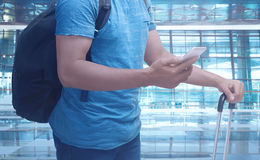 Man holding cellphone and suitcase. Travel concept image Royalty Free Stock Image