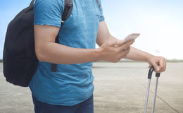 Man holding cellphone and suitcase. Travel concept image Stock Images