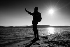 Man holding cellphone, taking picture of autumn sunset or sunrise in picturesque sea scenery Stock Photo