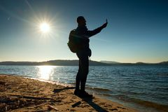 Man holding cellphone, taking picture of autumn sunset or sunrise in picturesque sea scenery Royalty Free Stock Photo