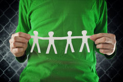 Man holding chain of people paper cuts Stock Images