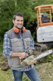 Man holding chainsaw wearing ear protectors. Man royalty free stock photos